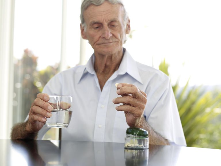 Elderly man taking a medicine with a cup of water