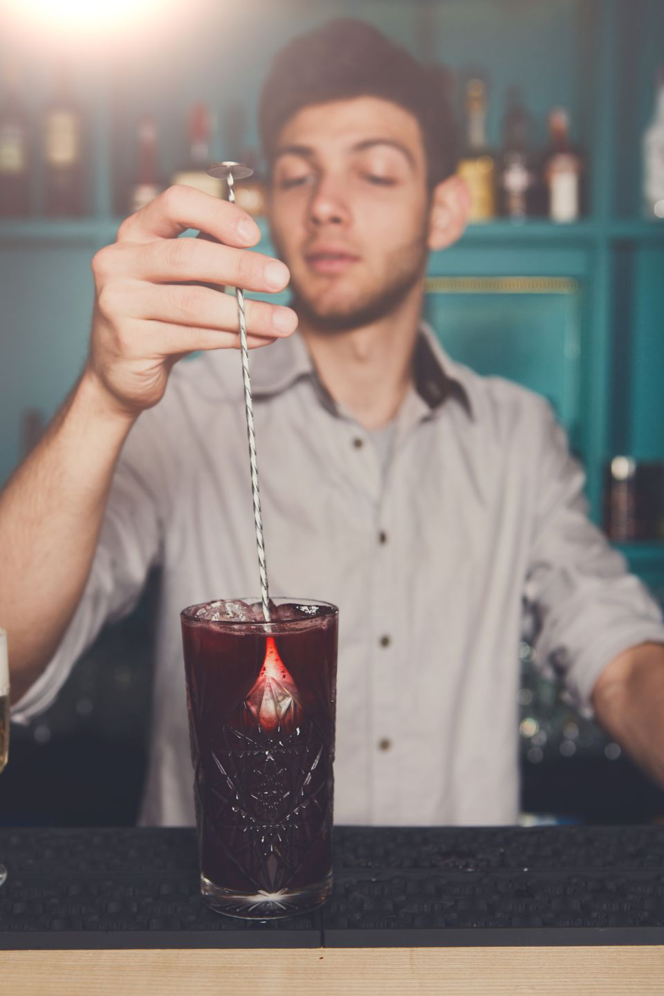 Young male bartender stirring cocktail with a bar spoon.