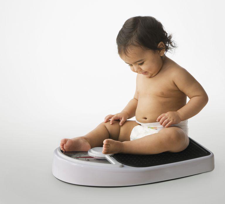 Hispanic baby girl sitting on a scale