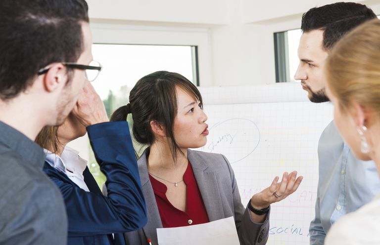 Image is of a group of business people engaged in serious conversation.