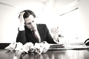 a man looking frustrated with at a desk with crumpled papers in front of him