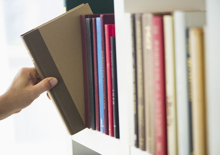 hand removing book from shelf