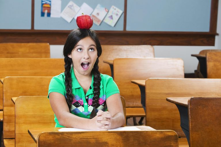 Schoolgirl carrying an apple on her head in a classroom