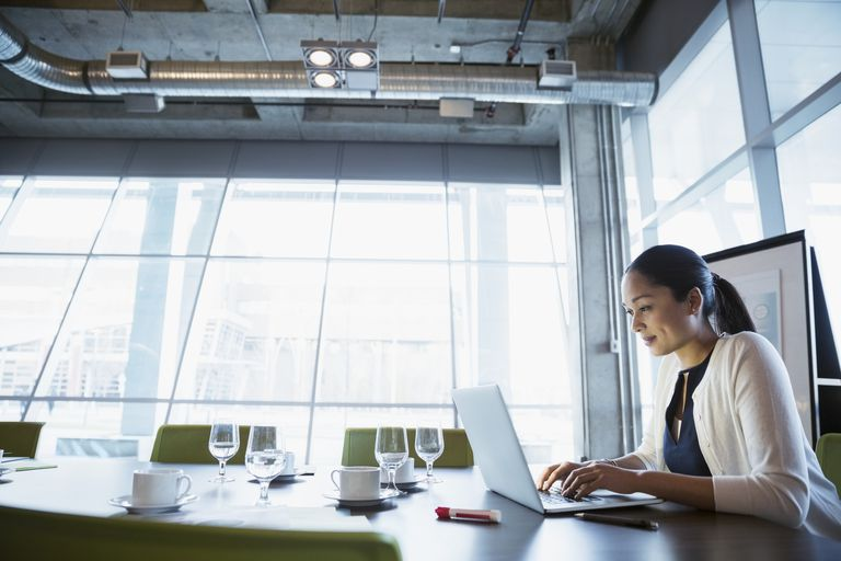 Woman on laptop in conference room