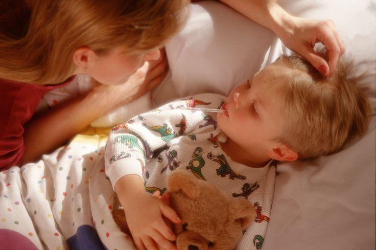 Boy (3-5) having temperature taken by mother