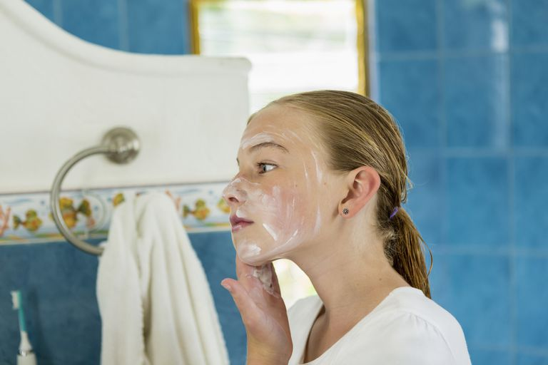 Caucasian girl washing face with soap