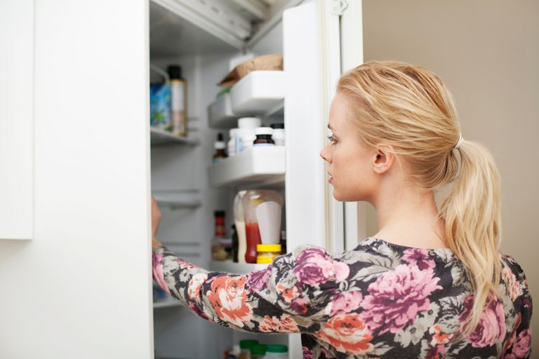 Woman with food addiction reaching into fridge
