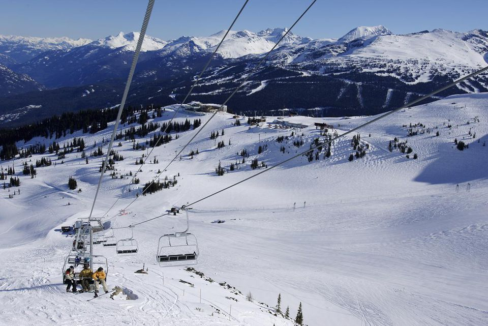 A group of snowboarder on chair lift on Whistler Mountain