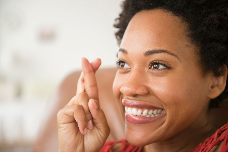 Close up of Black woman smiling with fingers crossed.