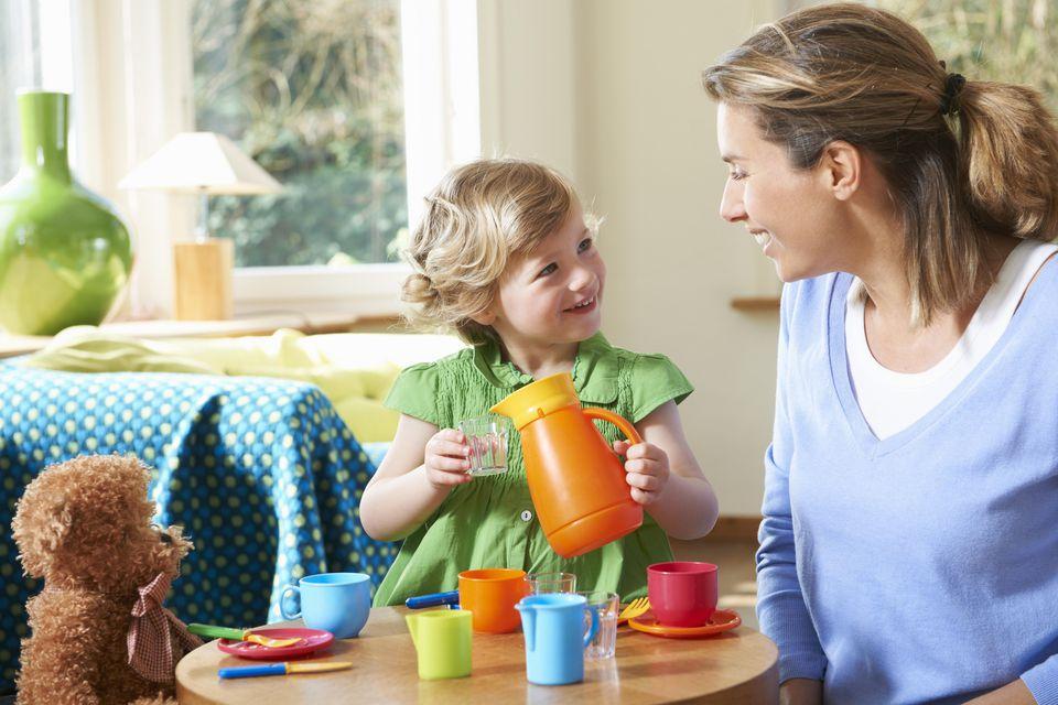 Mother, daughter, teddy bear playing tea-parties