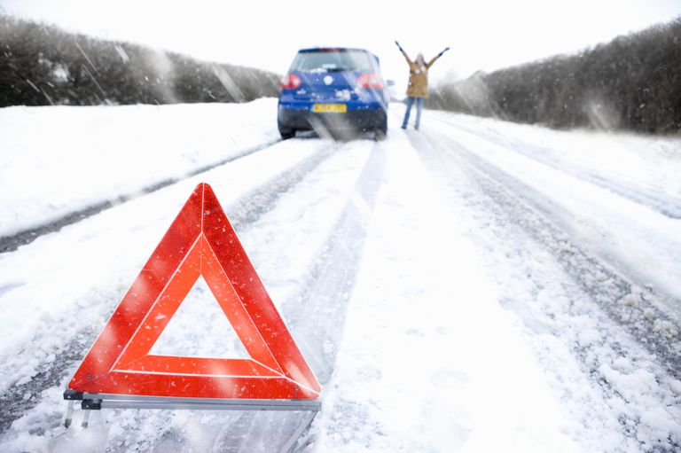 woman gesturing for help outside a blue car on a snowy road