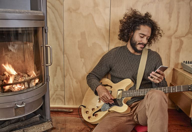 Young man with electric guitar looking at cell phone