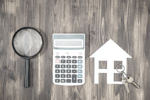 Mortgage calculations concept, calculator with magnifier and cutout of home