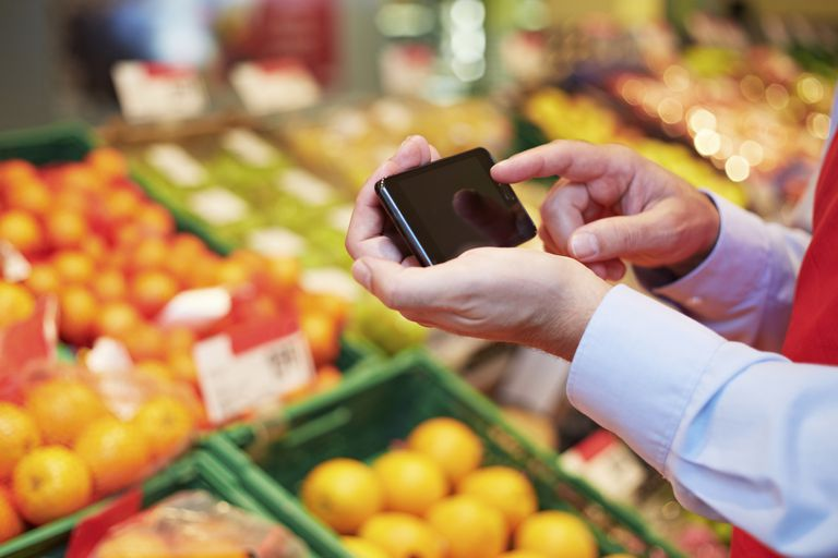 Person using smartphone in grocery store.
