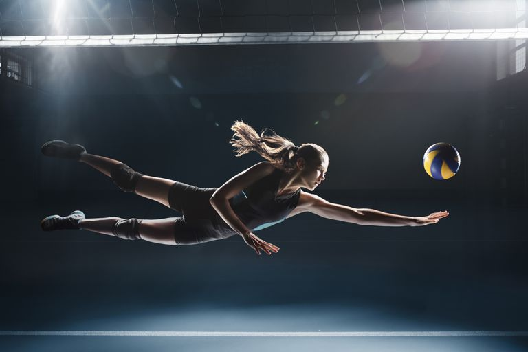 Girl diving for volleyball