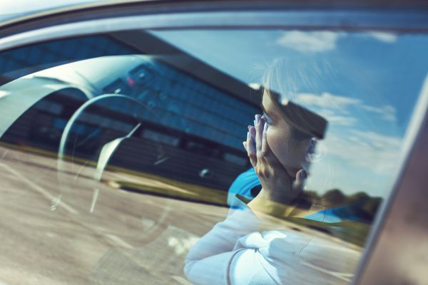 distressed woman sitting in car with hands over her face