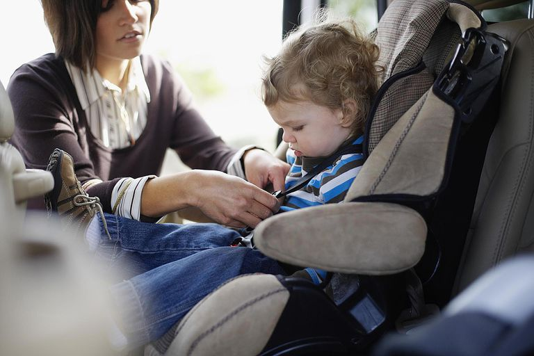 Mother Putting Son in Car Seat