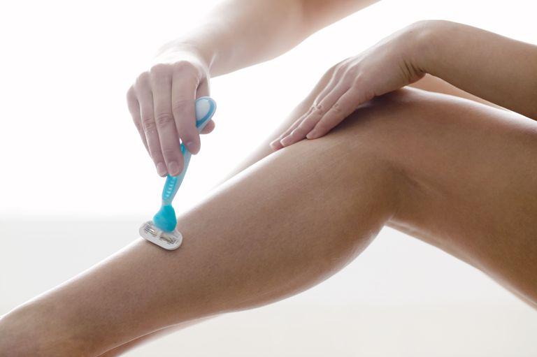 Teenaged girl shaving her legs
