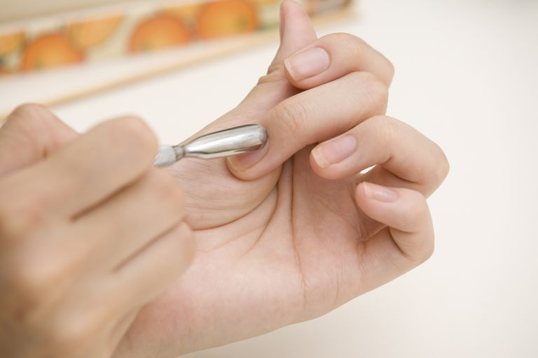 Woman using cuticle pusher