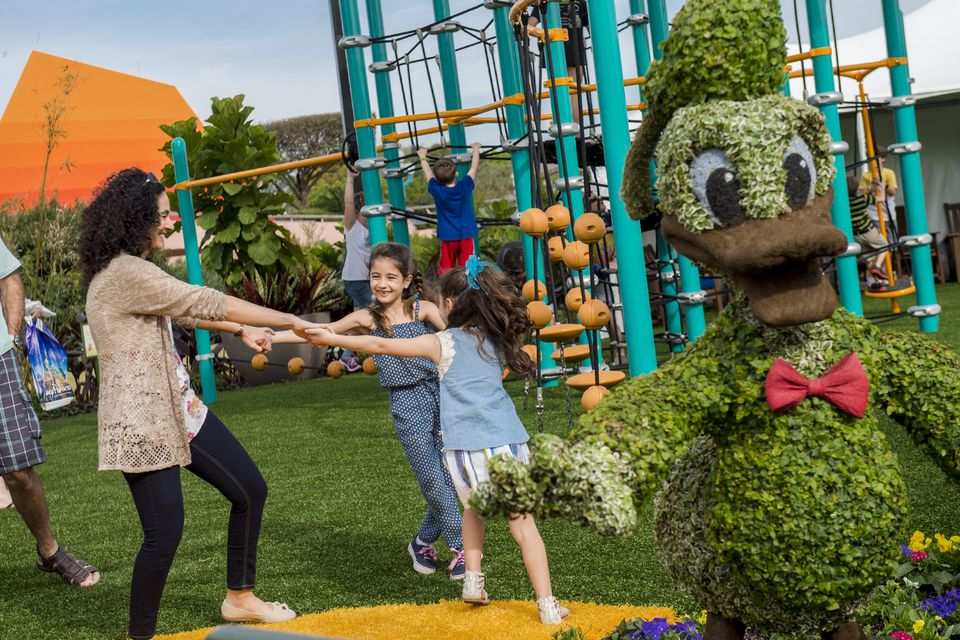 A mom and daughters enjoy playground at Epcot International Flower & Garden Festival