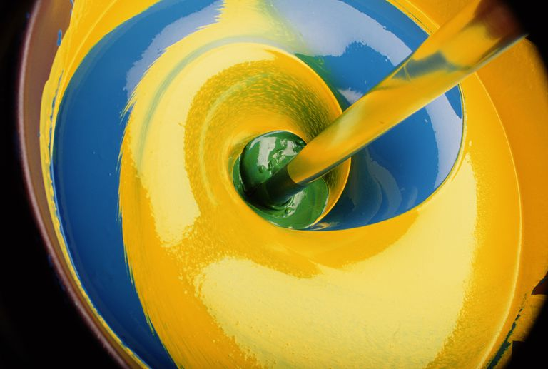 Swirl of yellow and blue paint producing green, close-up