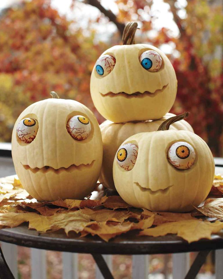 A trio of zombie pumpkins sitting on a table.
