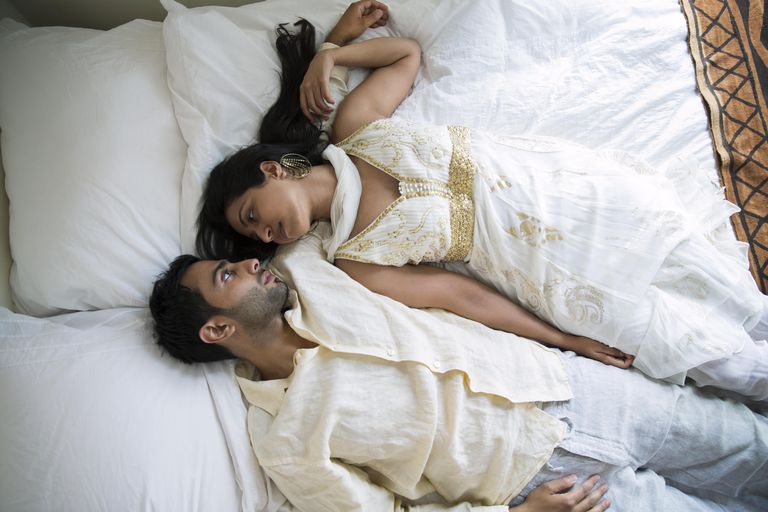 Indian Couple Laying Together on a Bed