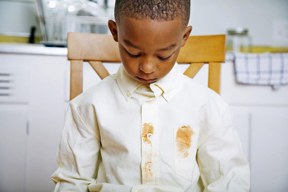 Young Boy Looking at Shirt's Food Stains