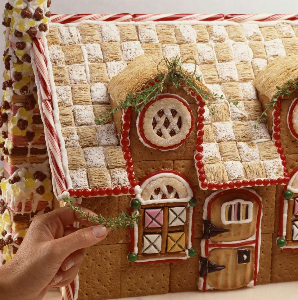 Person decorating gingerbread house