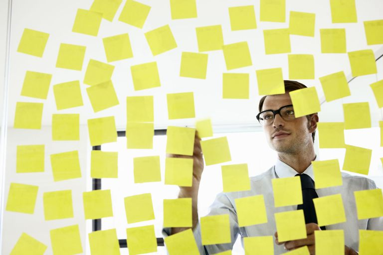 project manager analyzing project tasks written on sticky notes