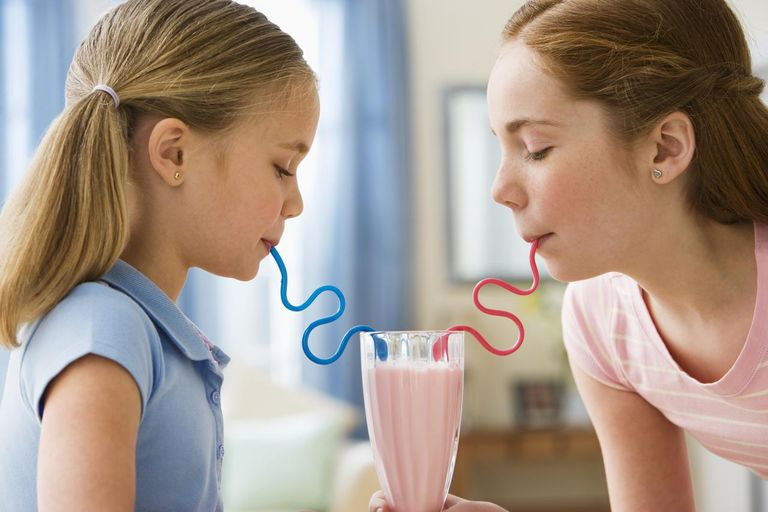 Two sisters drinking with straws from same glass, side view, close-up