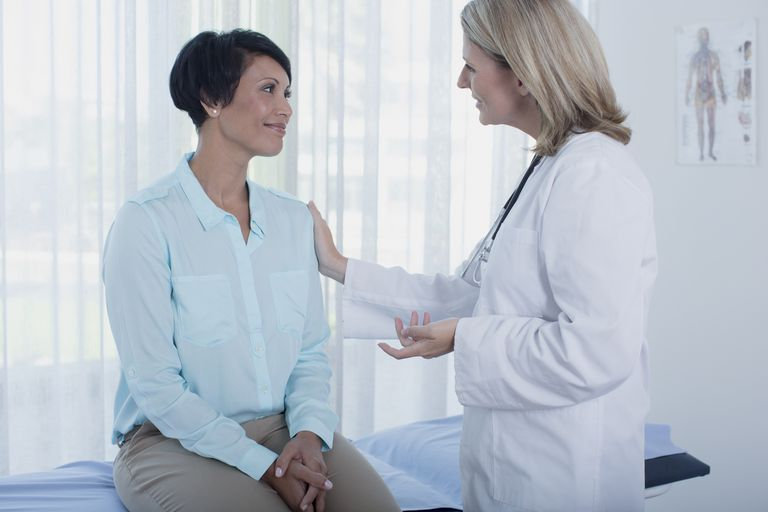 Smiling female doctor talking to patient in office