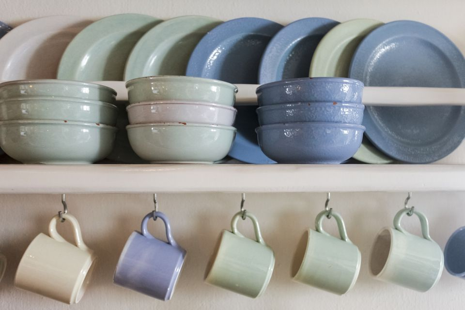 Blue and green plates, bowls and coffee cups on shelf