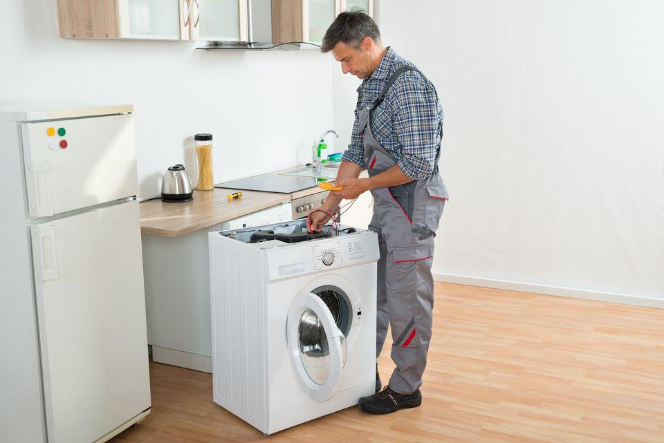 Technician Checking Washing Machine With Digital Multimeter