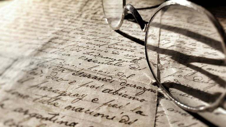 Close-Up Of Eyeglasses On Letter