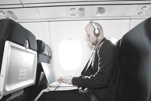 Businessman on aeroplane, wearing headphones and using laptop computer