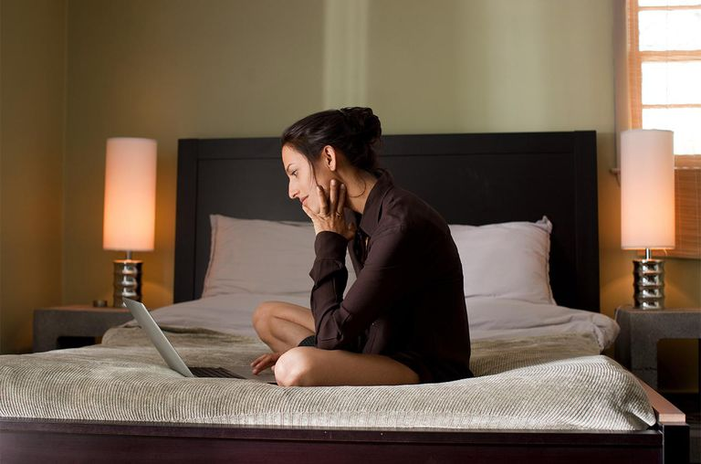 Woman sitting on bed using laptop