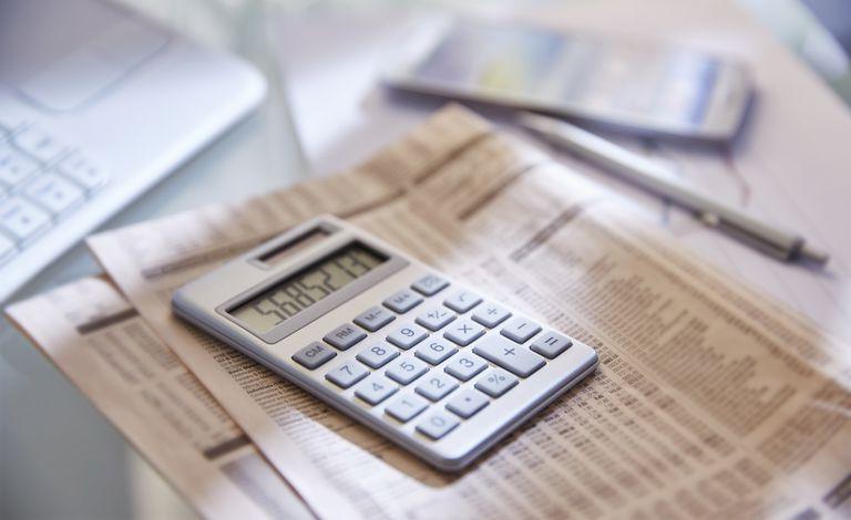 Calculator, close up, newspaper and pen on desk