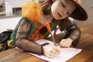 A girl in a Halloween costume completing a math worksheet.