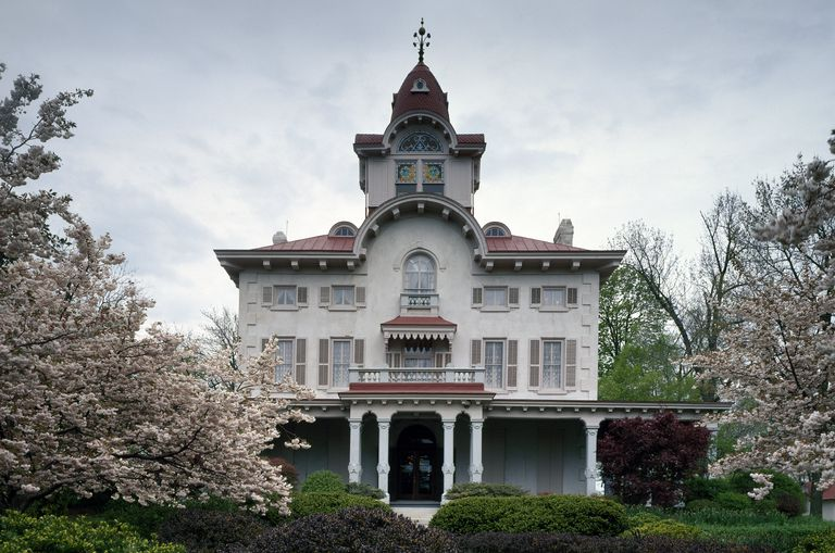 Two 1/2 story Italianate mansion with arched central tower protruding from a slightly sloped roof