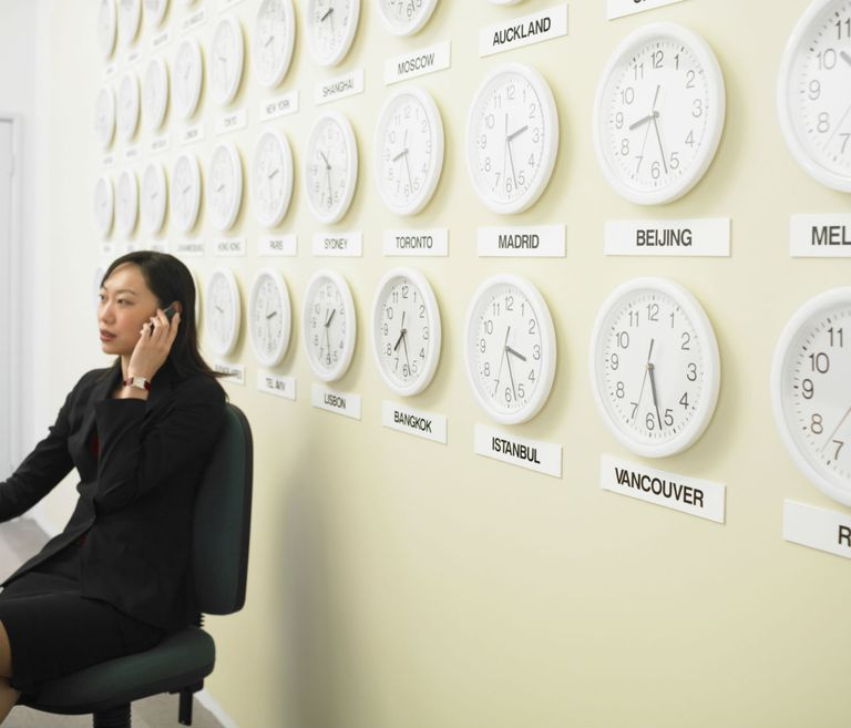 Businesswoman on the phone with a wall of country clocks behind her