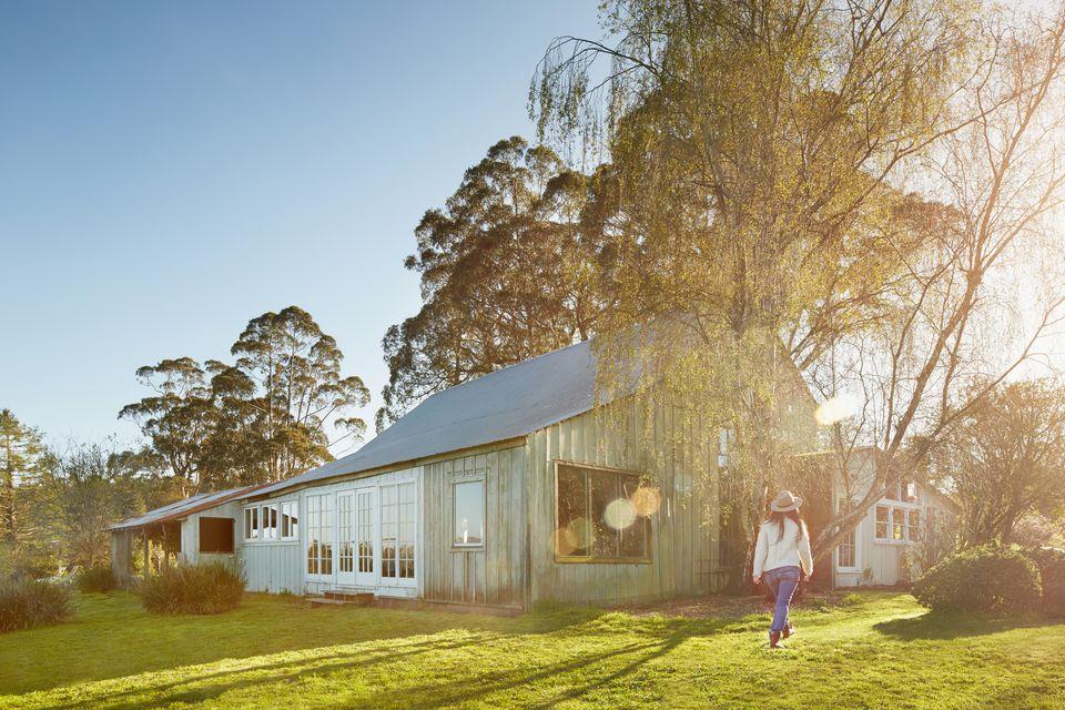 Woman walking in backyard of barn house