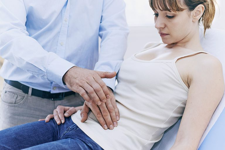 doctor doing abdominal check on a woman