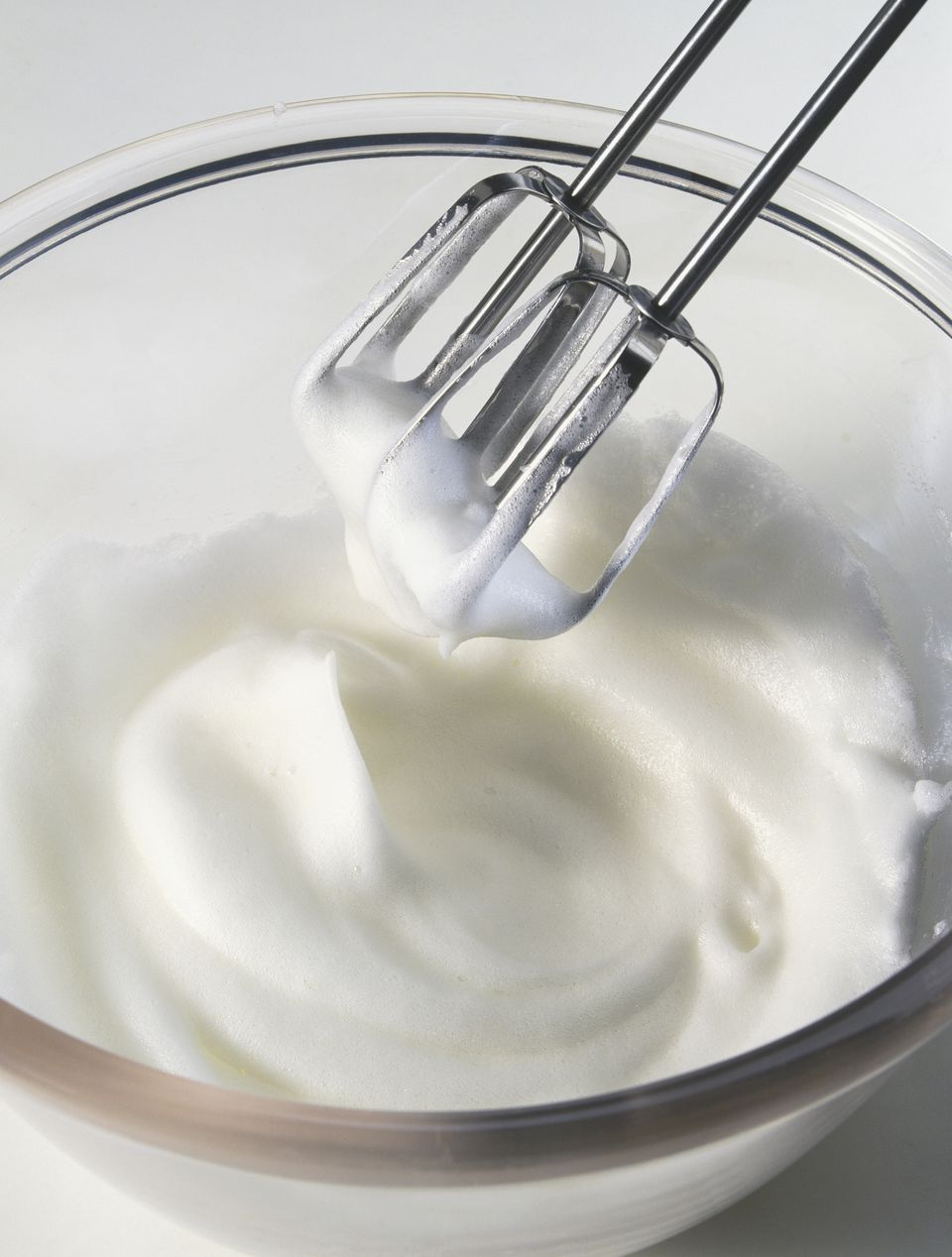 Electric mixer whisks lifted from whisked egg whites mixture, close up.