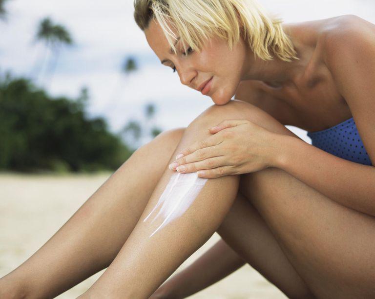 Woman applying sunscreen lotion to leg