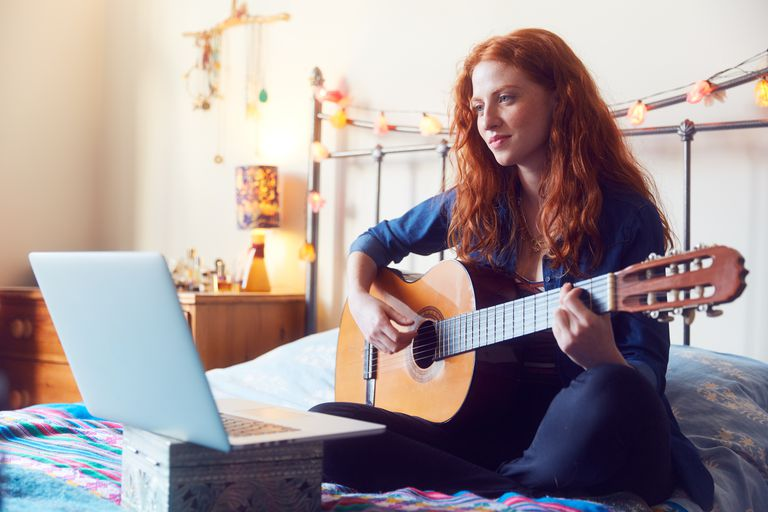 Young woman on bed with guitar and laptop