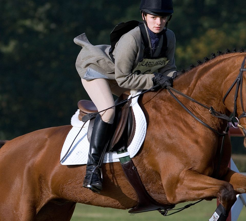 Girl in English riding clothes, riding a horse as it jumps an obstacle.