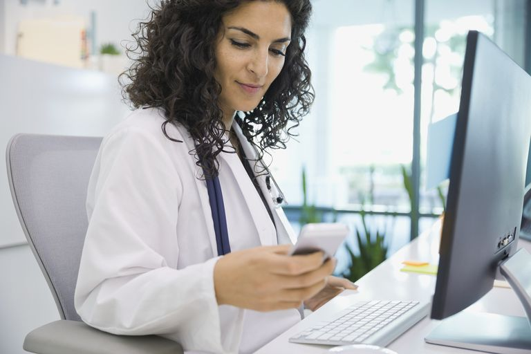 doctor using smartphone in front of computer