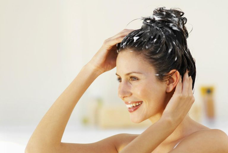Side view of a woman scrubbing her hair