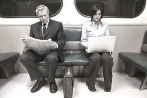 2 people on subway with news and computer